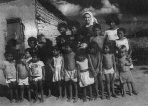 Foto in bianco e nero di Suor Daniela in visita ad un gruppo di bimbi