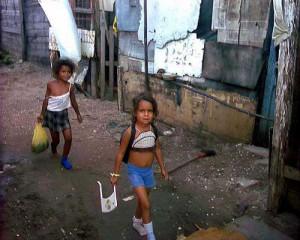 bambine camminano per le strade sporche di una favela, indossando abiti stracciati e senza scarpe